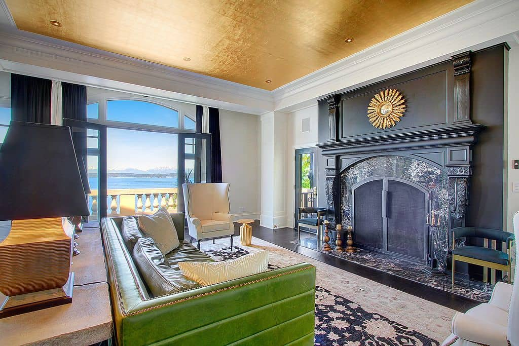 Eclectic living room features gold tray ceiling and glass double door that opens to the balcony with a stunning ocean view. It has white wingback chair and an elegant green sofa that faces the black arched fireplace accented with a sunburst mirror.