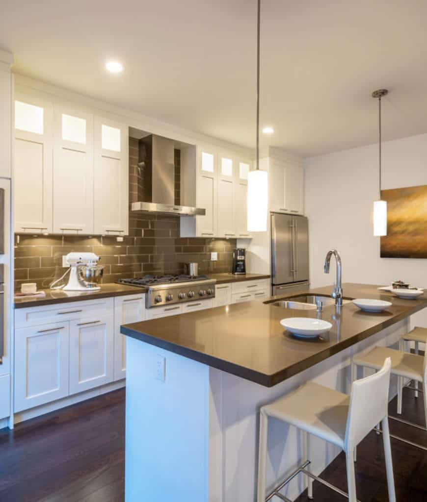 This kitchen offers white central island and cabinetry contrasted with black countertops and subway tile backsplash that's mounted with a stainless steel range hood.