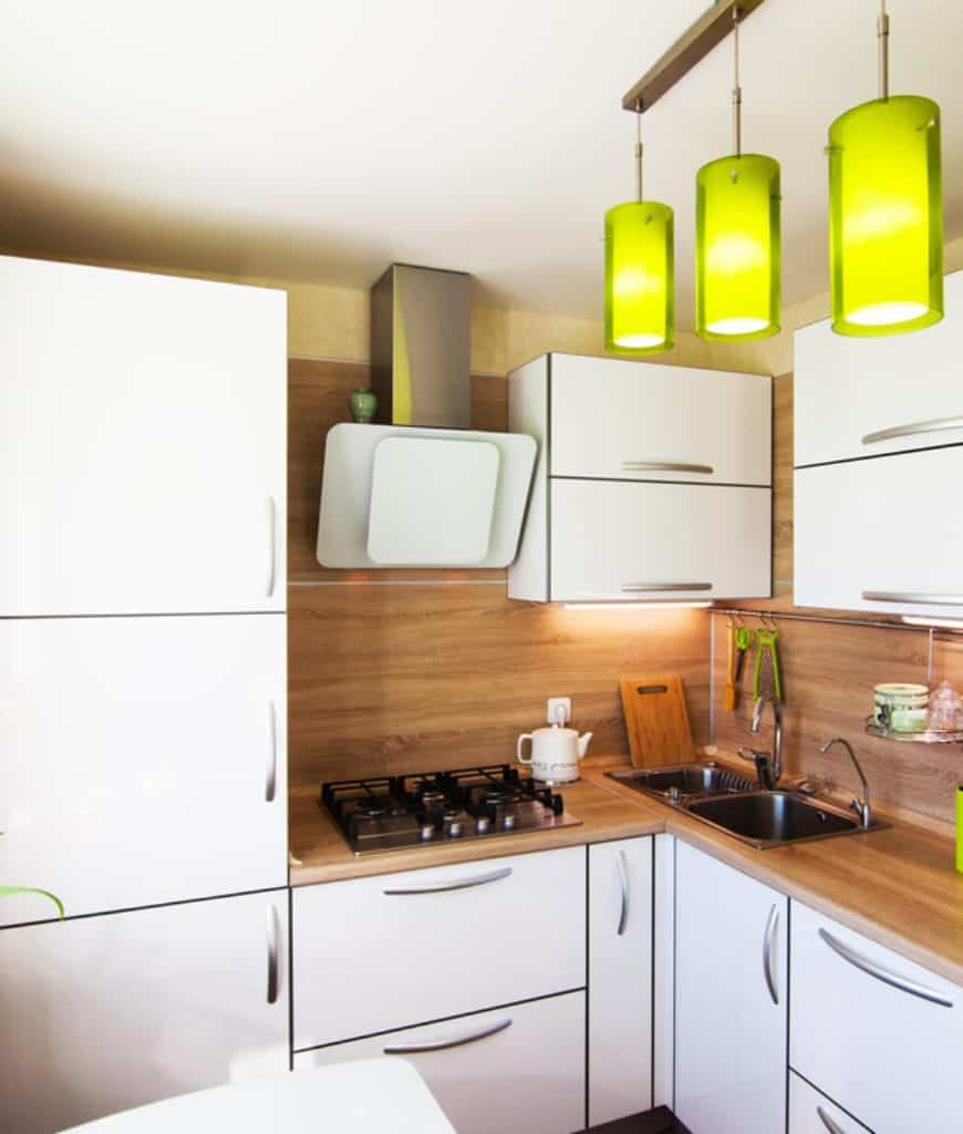 Green cylindrical pendants stand out in this kitchen showcasing white cabinetry with chrome pulls and wooden counter fitted with dual sink and cooktop.