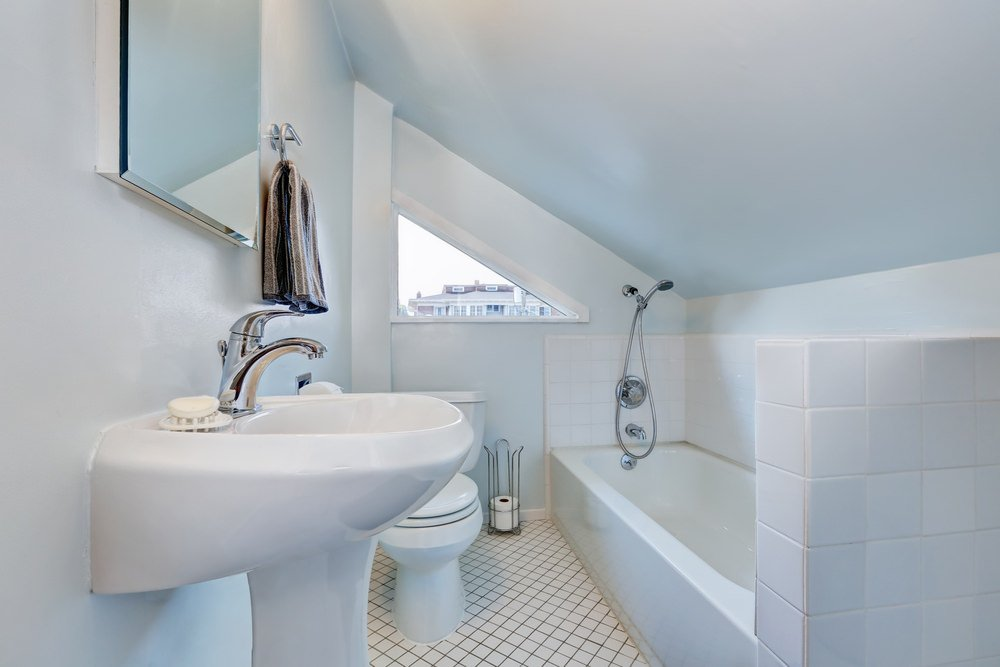 A small bathroom featuring a corner tub and shower combo and a pedestal sink both under the shed ceiling.