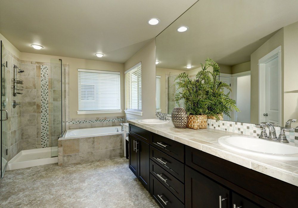 This master bathroom boasts stylish flooring, a bathtub and a walk-in shower in the corner. There are two sinks with marble tiles countertop as well.
