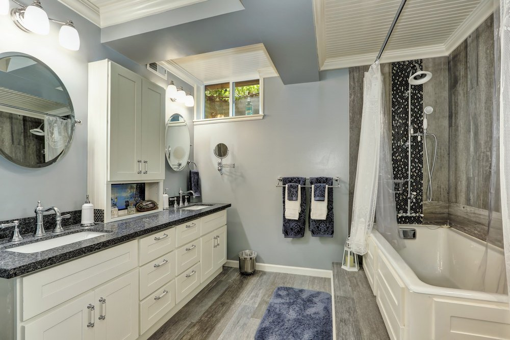 This primary bathroom boasts two sinks with granite countertop. The hardwood flooring looks perfect together with the walls. There's a corner tub with rustic walls as well.