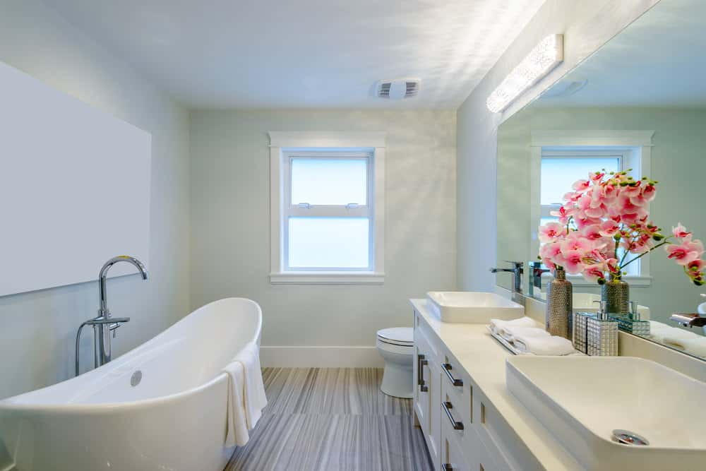 This primary bathroom offers a freestanding tub and double vessel sinks with lovely flowers in a vase.