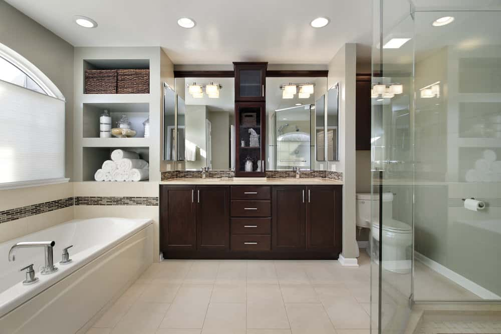 A spacious master bathroom featuring a deep soaking tub, a walk-in shower and two sinks on a smooth beige sink countertop lighted by wall lights and recessed lights.