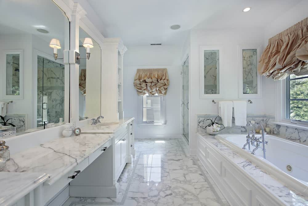 White primary bathroom boasting marble tiles flooring and marble sink countertops. There's a drop-in tub near the windows and a walk-in corner shower.