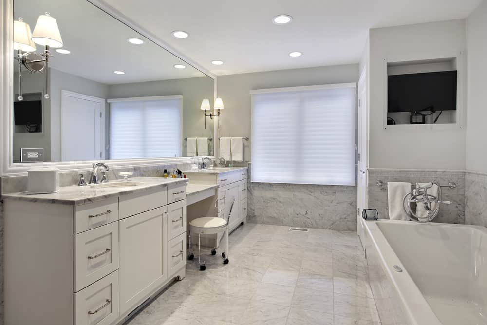 Large master bathroom featuring marble tiles flooring and countertops. There's a corner soaking tub along with two sinks lighted by wall and recessed lights.
