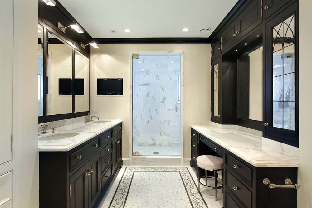 Small master bathroom featuring two sinks on a marble counter and a powder desk, along with a walk-in shower.