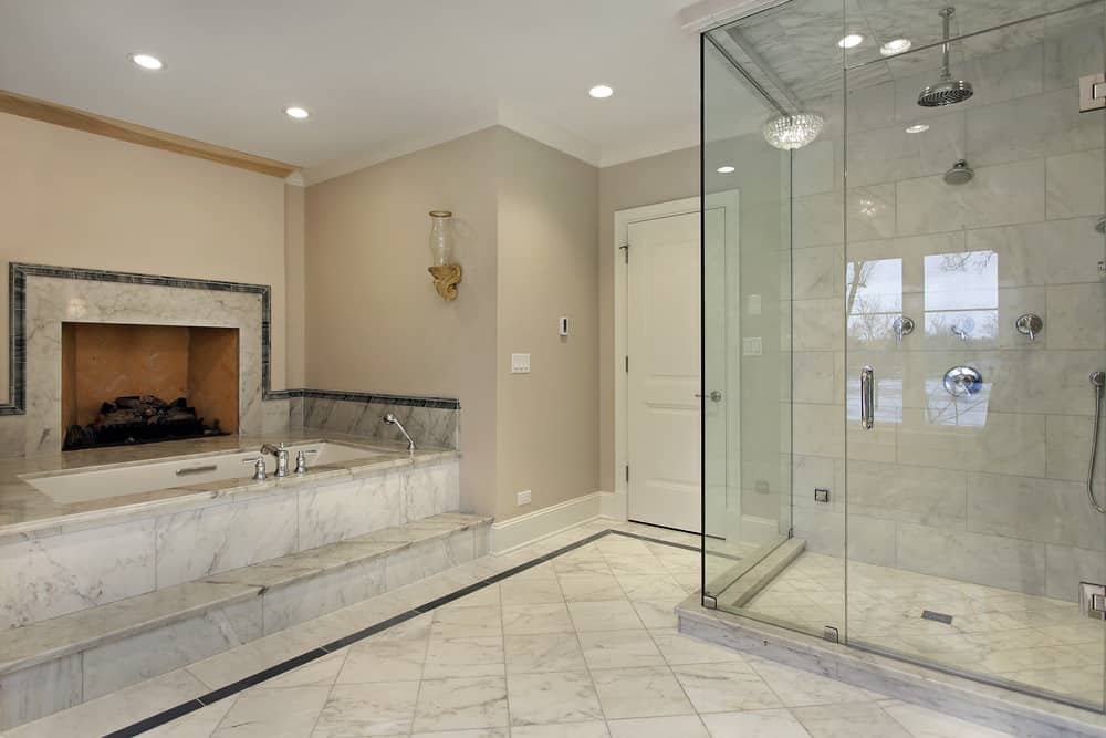 Spacious primary bathroom featuring marble tiles flooring and gray walls. The room has a drop-in tub with a fireplace on its side and a walk-in shower.