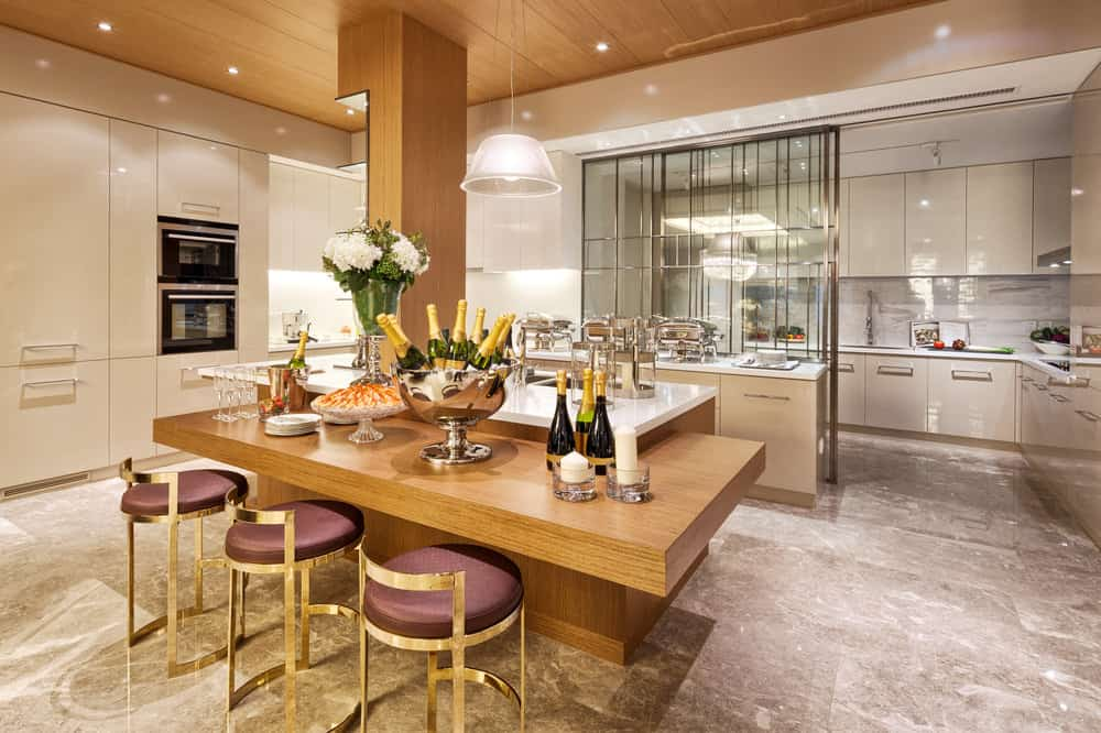Luxurious dining room with two-tiered counters lined with gold metal stools. It is lighted by a white pendant that hung from the wood ceiling along with recessed lights
