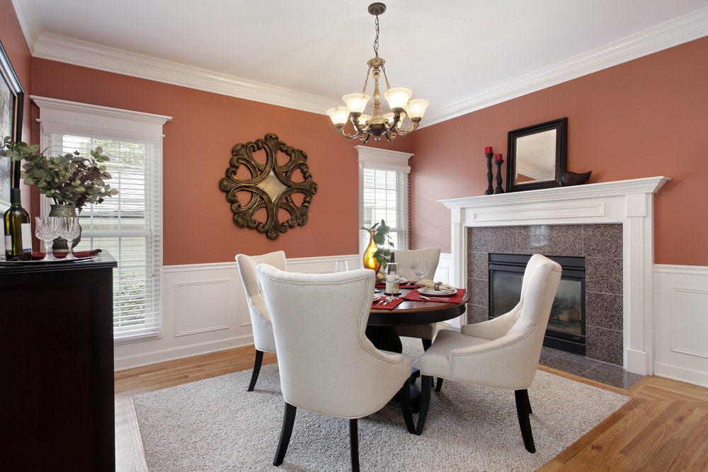 Charming dining room decorated with a round wood wall art mounted on the coral pink wall. It has a round dining table surrounded with white wingback chairs that sit on a gray rug and beside the fireplace.