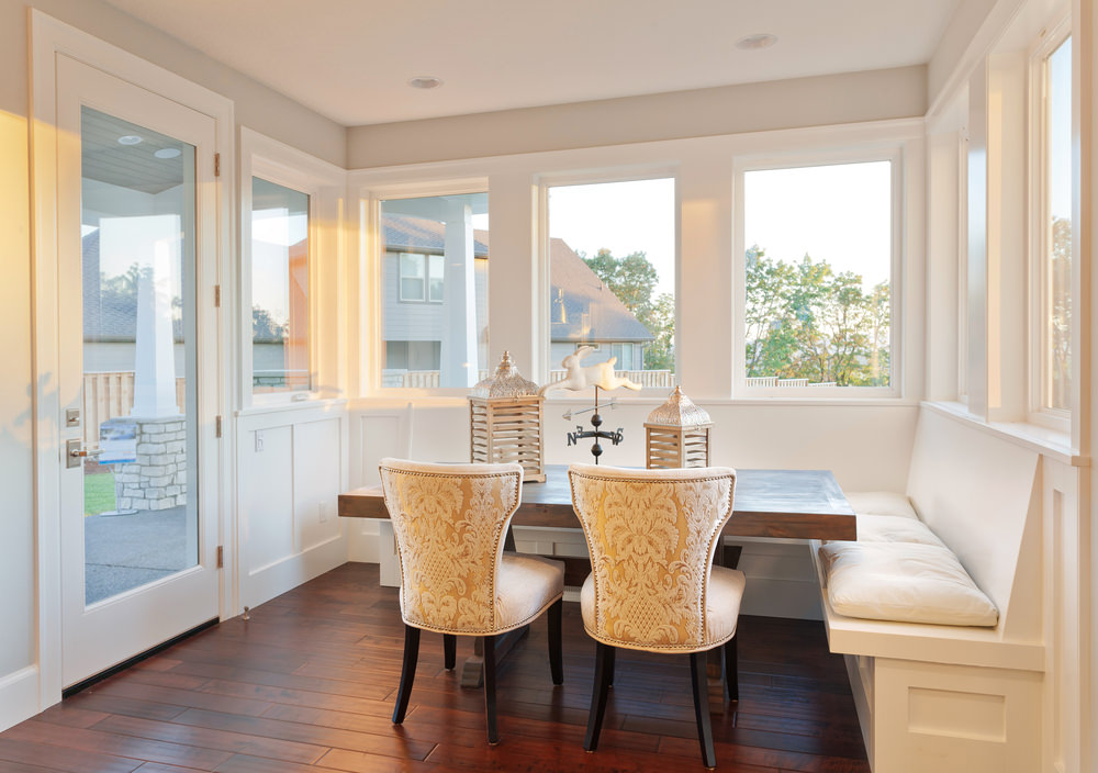 White dining area surrounded with glass windows and door bringing plenty of natural light in. It has a natural wood dining table paired with white classy chairs and built-in bench topped with white sectional cushions.