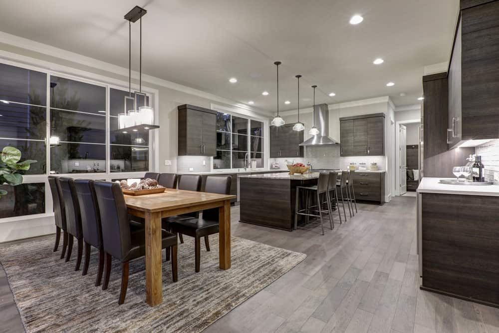 Open dining area with natural wood dining table paired with black leather chairs. It has a dark hardwood flooring topped with a taupe rug.