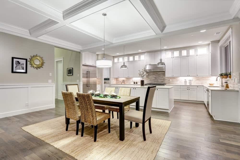An eat-in kitchen with wood plank flooring topped with a tan rug and coffered ceiling with a hanging drum pendant. It includes a wooden table paired with wicker and beige highback chairs.