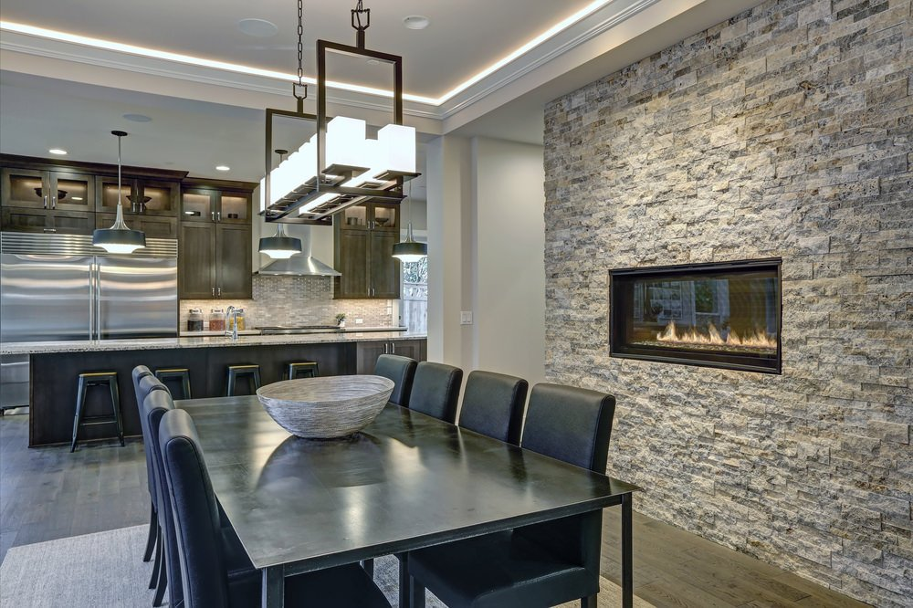 A dine-in kitchen features a modern fireplace fixed on the stone accent wall across the black dining set that's illuminated by a linear chandelier.