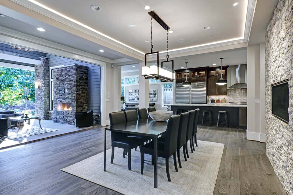 Elegant dining area with black dining table and chairs lighted by a linear chandelier that hung from a tray ceiling.