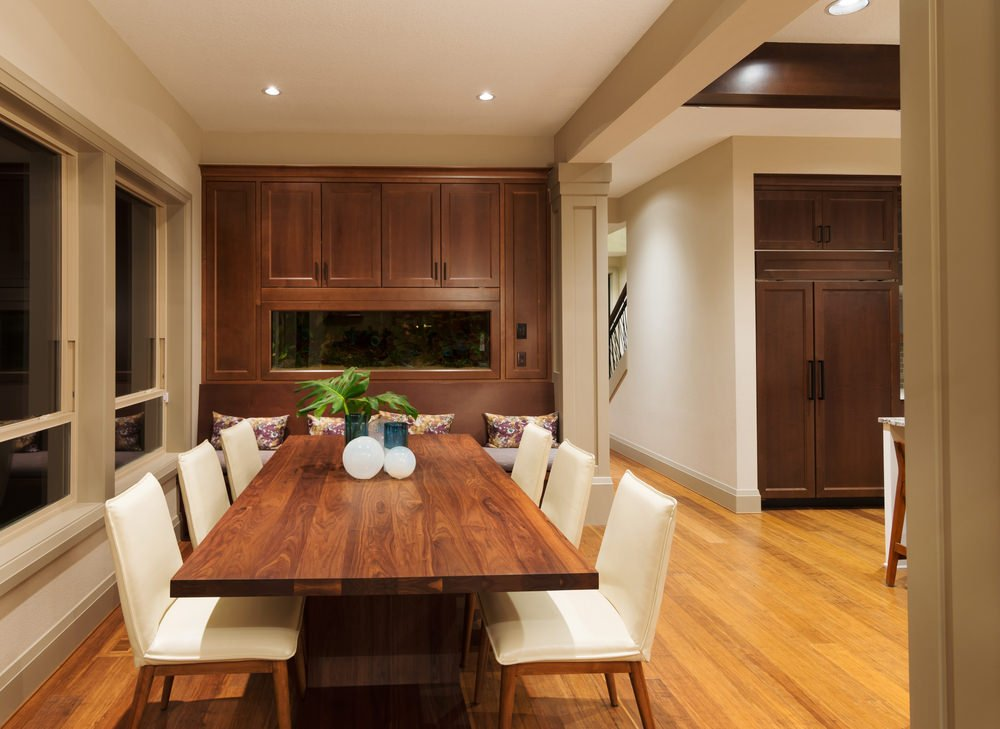 Cozy dining room showcases dark wood cabinetry fitted with a modern fireplace. It has a natural wood dining table and white upholstered chairs over hardwood flooring.
