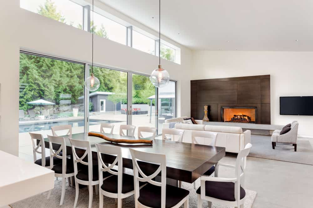 A pair of glass globe pendant light hung from a vaulted ceiling in this white dining space. It illuminates the dark wood dining table with black and white chairs.