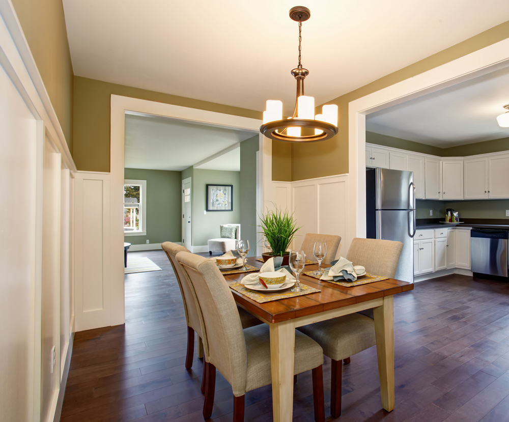 Gray upholstered chairs sit at the wooden table in this dining area lighted by a round candle chandelier. It has dark hardwood flooring and moss green walls above white wainscoting.