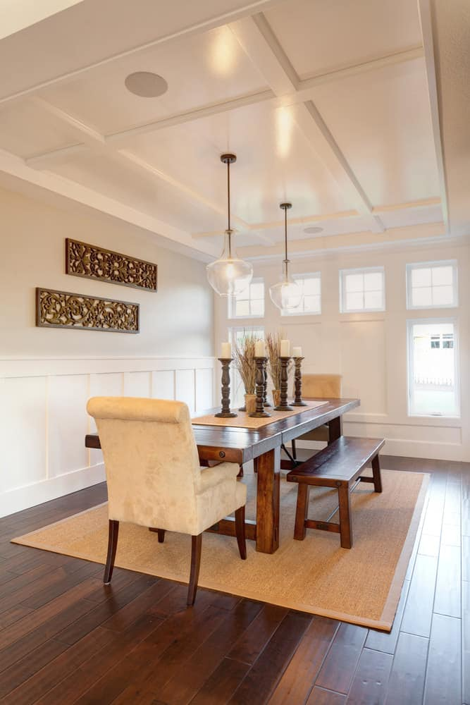 White dining room decorated with a carved wood wall arts mounted above wainscoting. It has wooden dining set with beige velvet accent chairs lighted by clear glass pendants.