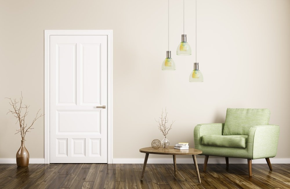 Minimalist entryway featuring hardwood flooring and beige walls. It offers a sitting area on the side lighted by charming pendant lights.