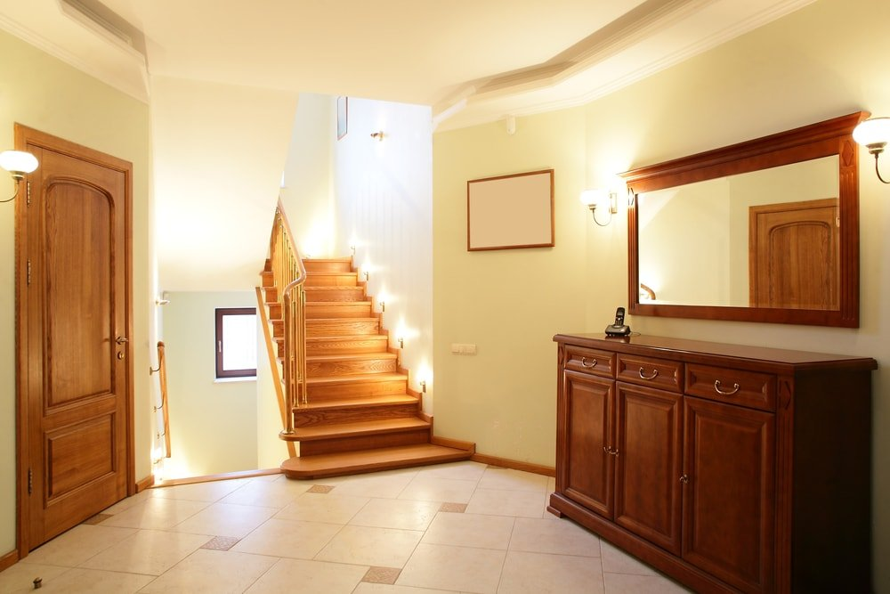 A simplistic foyer with bright wall lights illuminating the area. The foyer features tiles flooring.