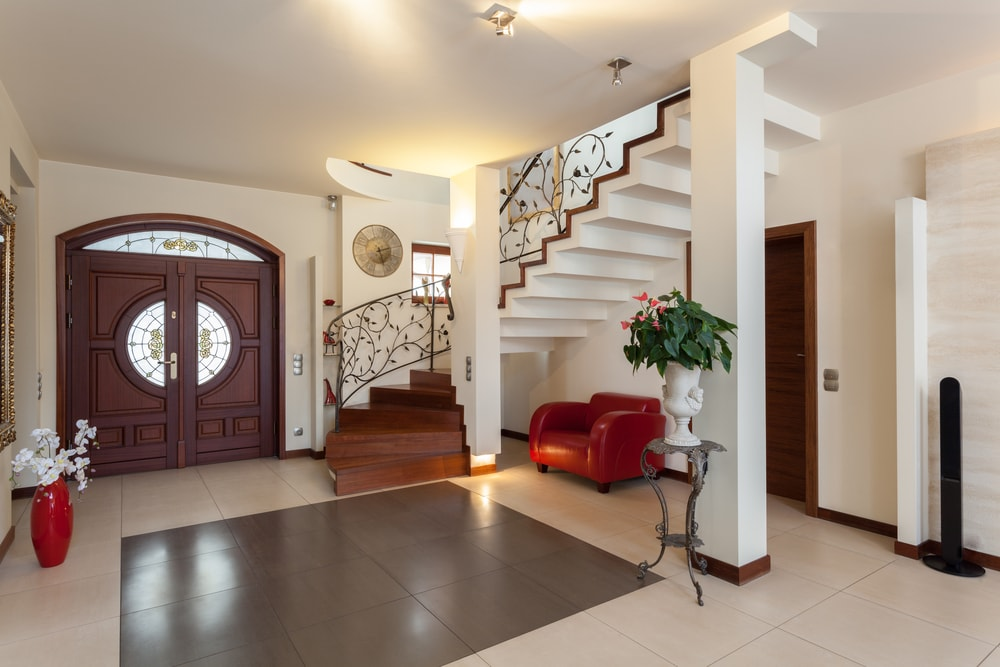 Spacious foyer with stylish tiles flooring and a winder staircase with elegant railings design. The area features white walls and a regular ceiling.