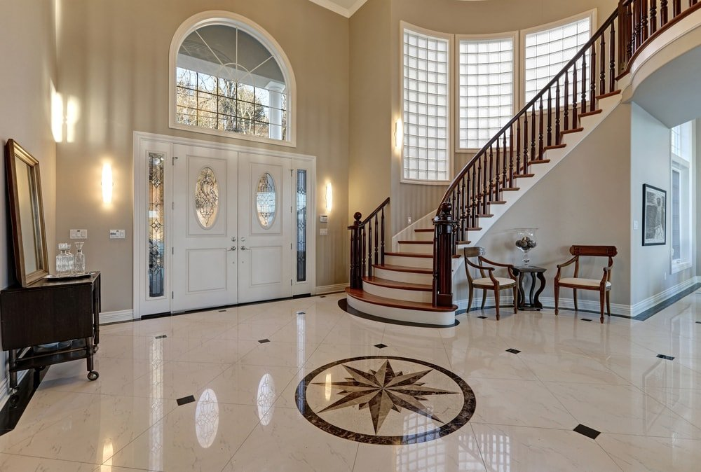 A beautiful foyer boasting stunning decorated tiles flooring, along with a curved staircase, surrounded by brown walls and a two-storey ceiling.