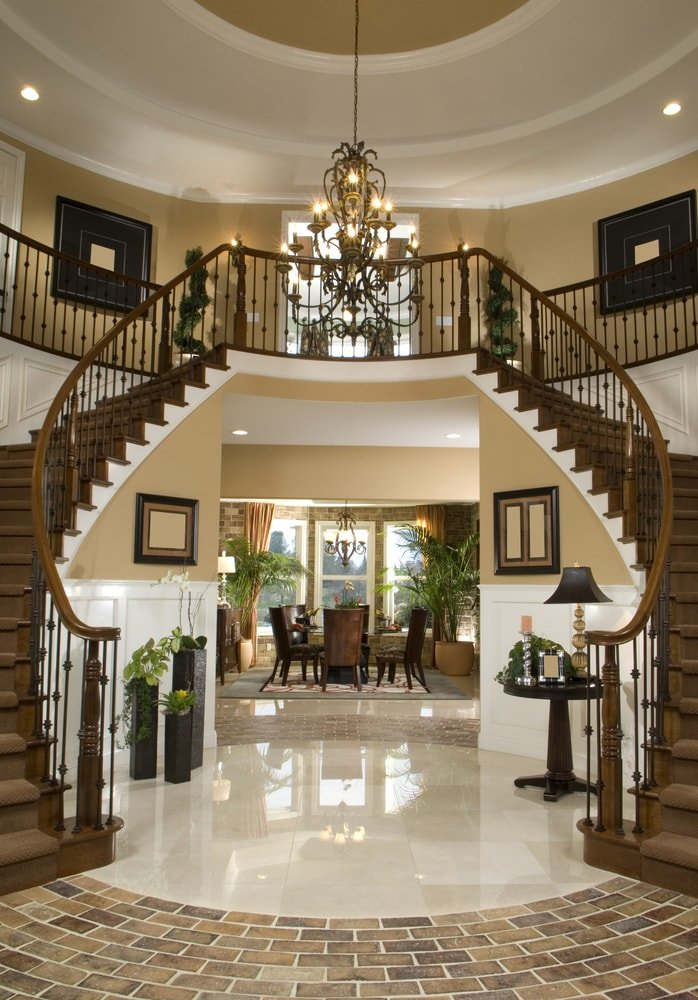 This grand foyer boasts a gorgeous staircase with hardwood carpeted steps and a glamorous chandelier light hanging from the stunning high ceiling.