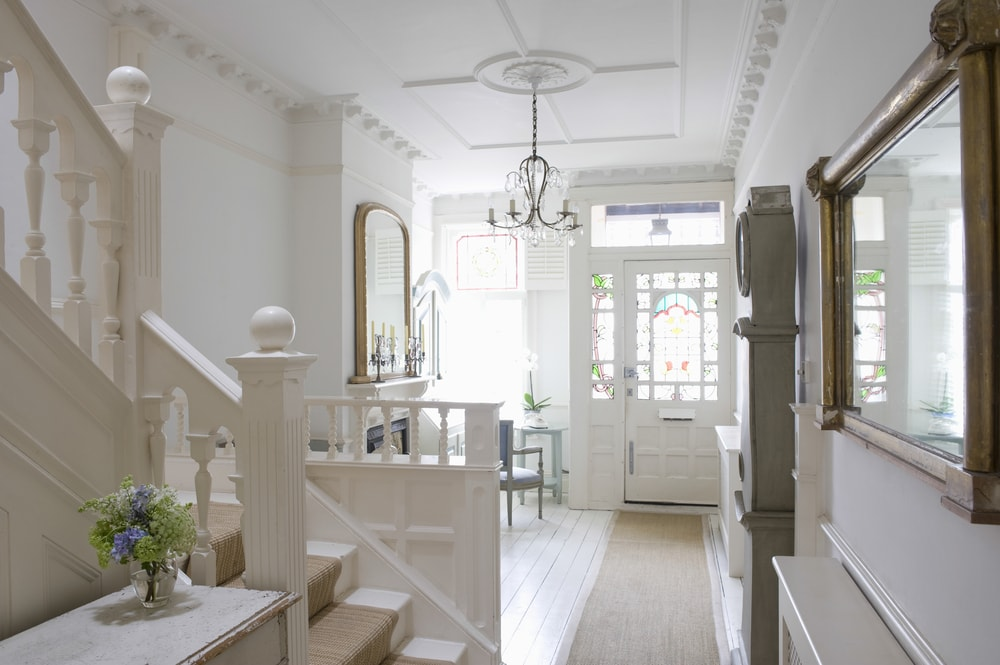 This home features a foyer with white walls and a lovely white ceiling. The area has a sitting area on the side featuring a fireplace, lighted by a chandelier.