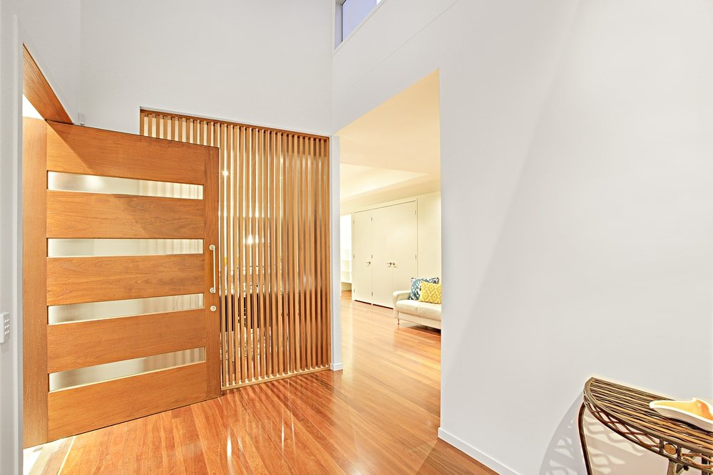 A contemporary house with a foyer featuring well-polished hardwood floors, white walls and a high ceiling.