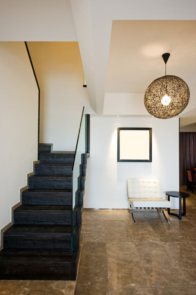 This foyer features brown tiles flooring with a pendant light, along with a staircase with dark hardwood steps.