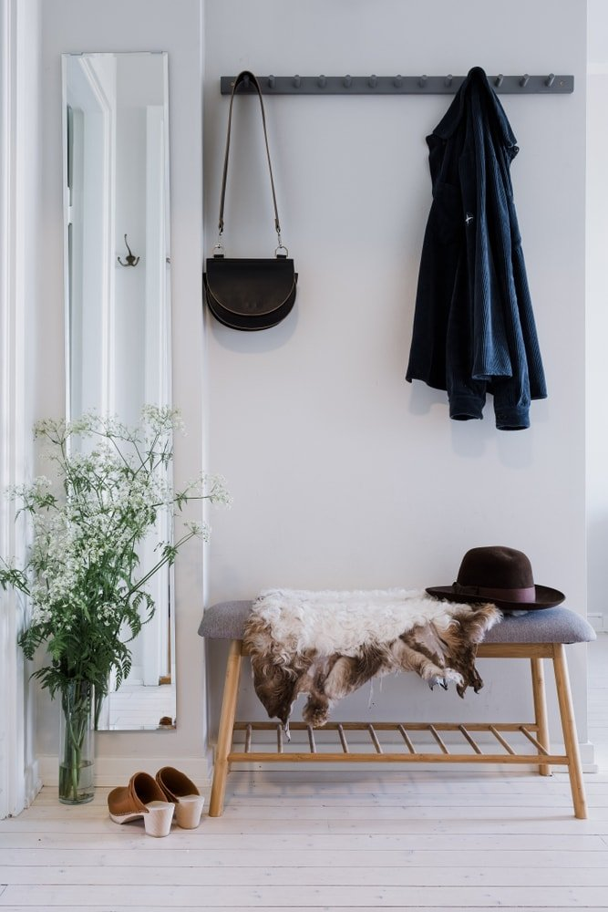 A modern mudroom area with a modern seating on the side. The area features hardwood floors and light gray walls.