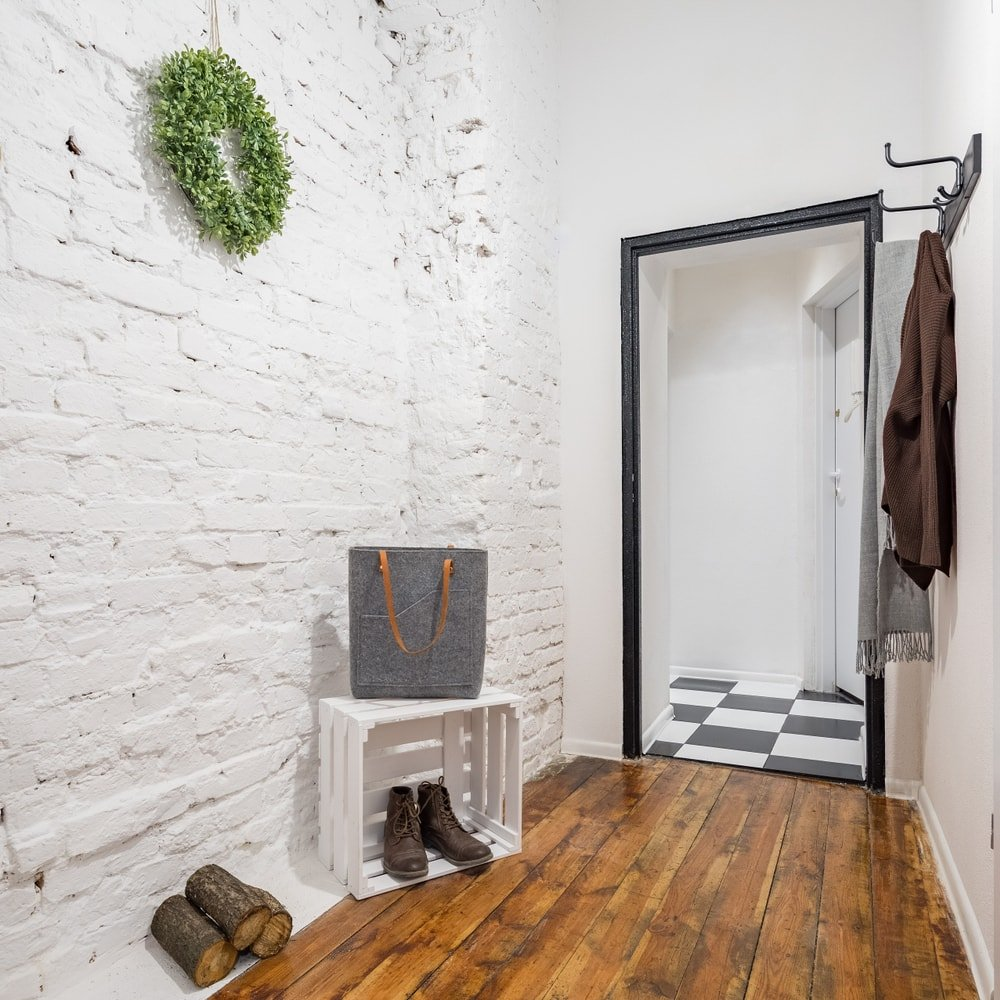 A mudroom featuring a white brick wall along with white concrete walls. The area also has hardwood floors and a tall ceiling.