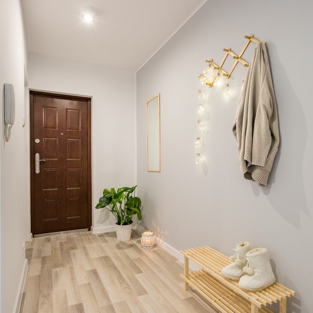 A mudroom featuring stylish hardwood floors and light gray walls. The lighting on the wall looks absolutely charming as well.