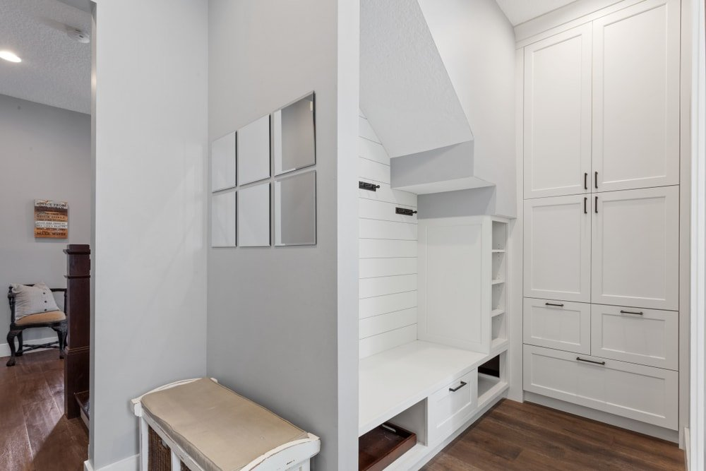 A mudroom featuring hardwood floors and light gray walls. It features a small seat on the side, along with built-in shelving and cabinetry.
