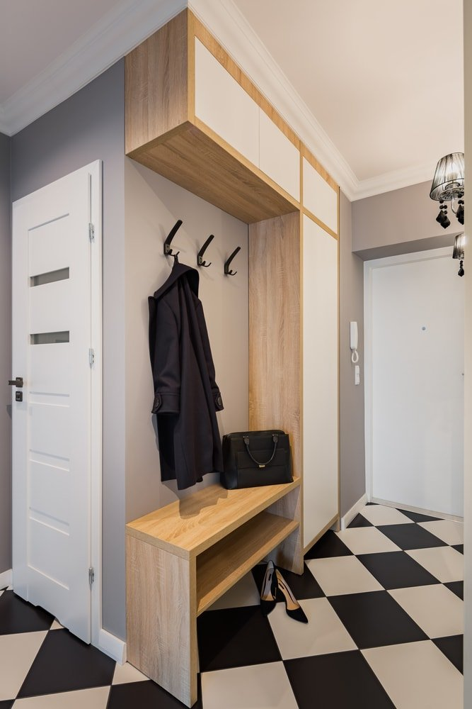A mudroom featuring checker tiles flooring and gray walls. The area is lighted by stylish wall lights.