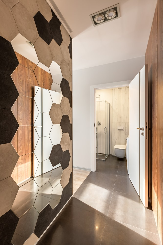 A mudroom featuring a hallway with a stylish wall with a mirror, along with tiles flooring. This hallway leads to the bathroom with a walk-in shower.