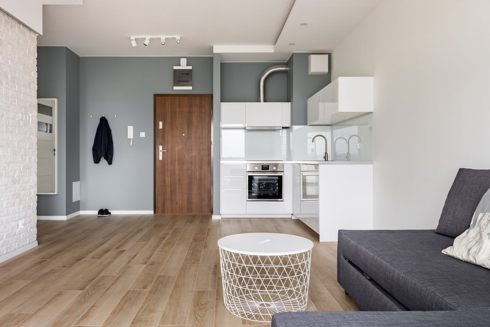 Spacious mudroom boasting a modern L-shaped sofa along with a white sink counter. The area features white and gray walls, along with hardwood flooring.