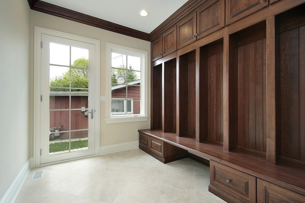 An empty mudroom area with a wooden built-in cabinetry and drawers. The area features beige walls and tiles flooring.