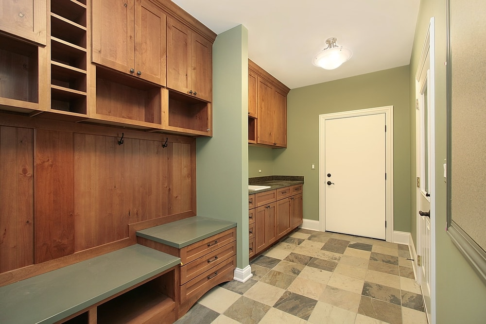 A mudroom featuring checker tiles flooring along with green walls and a regular ceiling. The area features a sink counter, together with cabinetry and built-in shelving. There's a bench seating as well.