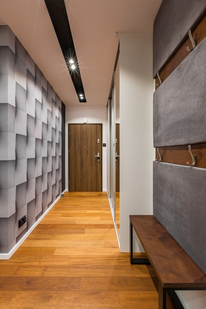 An entryway boasting a very stylish wall design, along with hardwood floors and a ceiling with track lights.