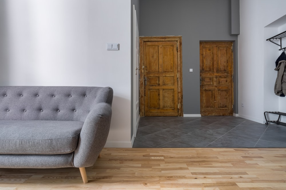 A spacious entry with gray tiles flooring and gray walls. It leads to the home's living space with a modern and elegant gray couch set on the home's hardwood flooring.