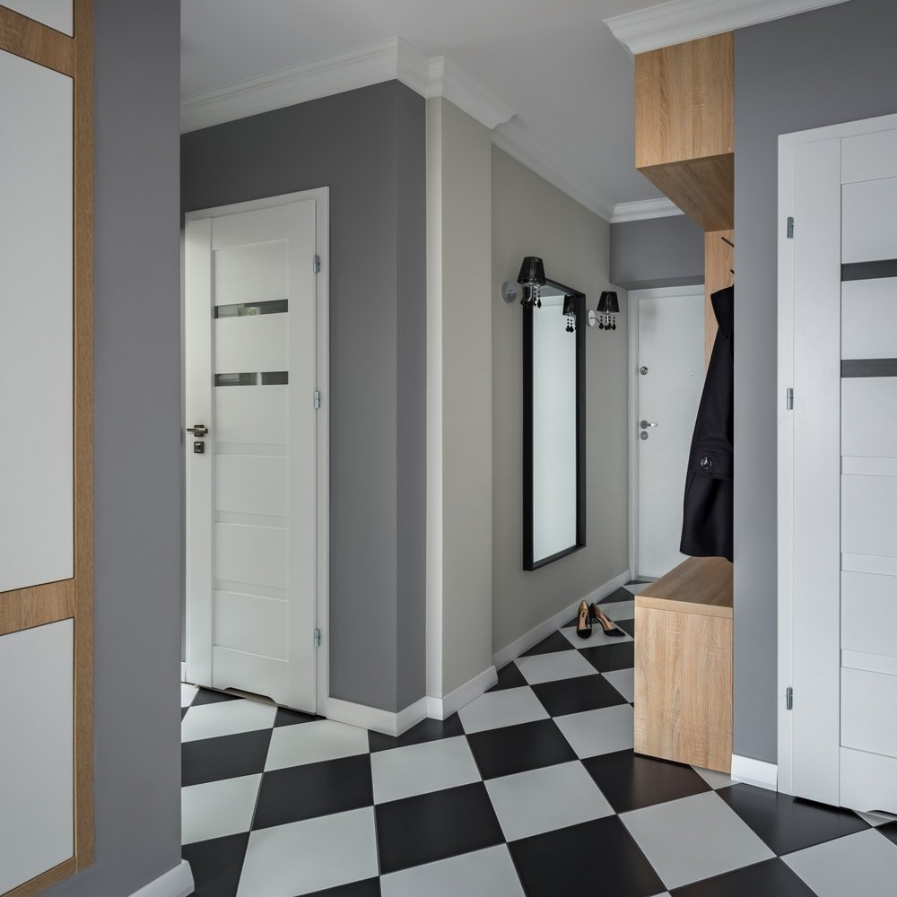 A mudroom that looks very modish, featuring checker tiles flooring and gray walls. It has built-in cabinetry and drawers, along with a built-in bench seating.