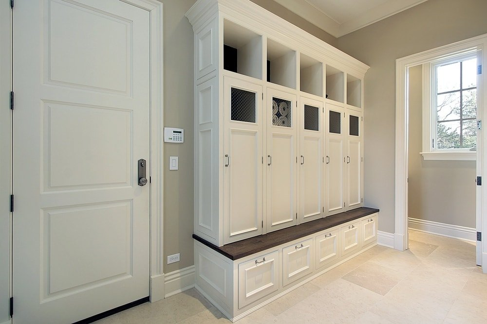 This mudroom offers built-in cabinetry and drawers, along with a built-in bench seating. The area features gray walls and tiles flooring.