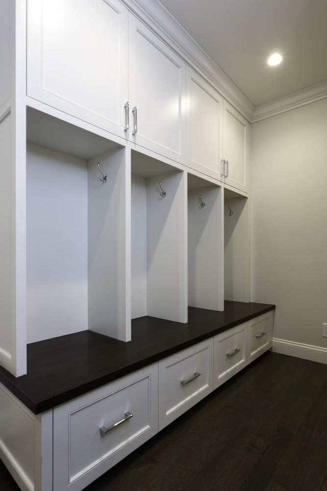 A closer look at this mudroom's bench seating with built-in cabinetry and drawers. The area features hardwood floors and is lighted by recessed ceiling lights.