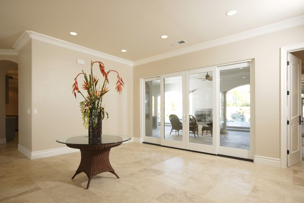 This entry features beige walls and tiles flooring, along with a centerpiece table set in front of the doorway.