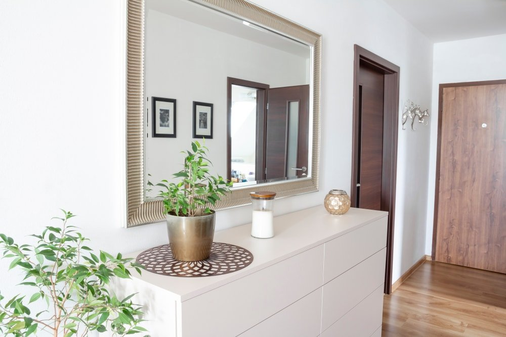 A closer look at this home's white side table topped by a small indoor potted plant. The area features white walls and hardwood floors.