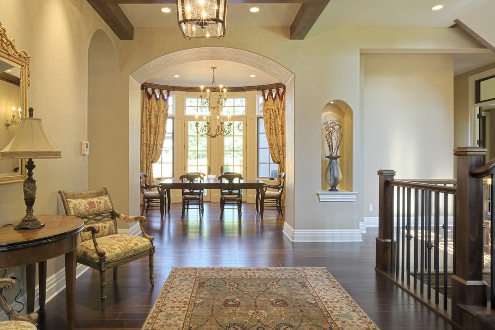 A Mediterranean home boasting a spacious entry with hardwood floors topped by a classy area rug, along with a tall ceiling with exposed beams.