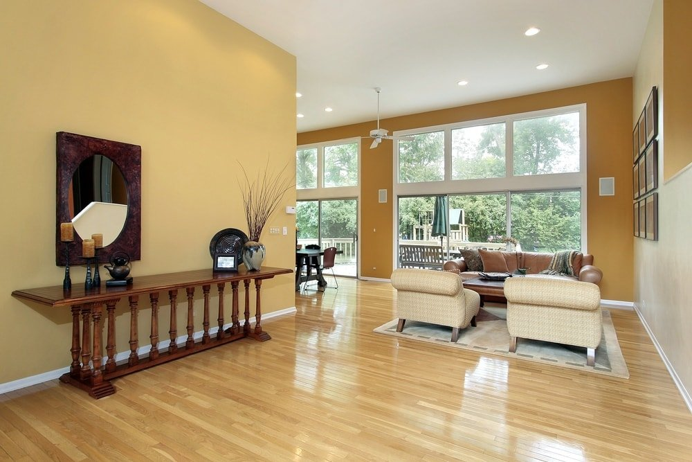 Spacious entryway boasting well-polished hardwood flooring and yellow walls surrounding the home. The ceiling features recessed ceiling lights. The hallway leads straight to the home's great room.