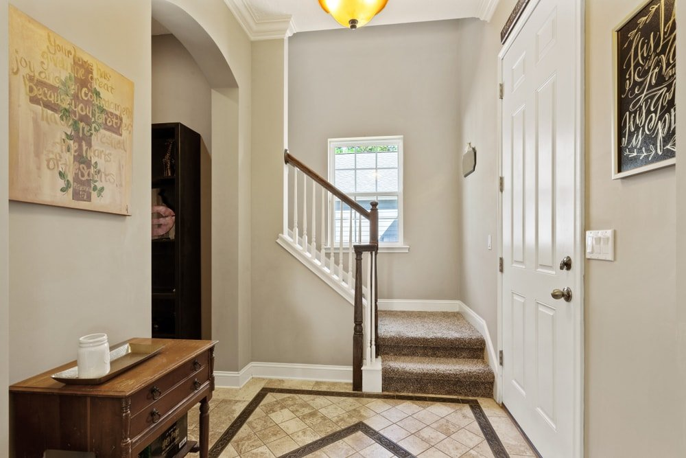 A small entry with decorated tiles flooring, light gray walls and a tall ceiling. It also offers an L-shaped staircase with carpeted steps.